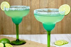 Margaritas with lime slices. Pair of margaritas with lime slices in a festive blue and green glasses against a wooden background Stock Photography