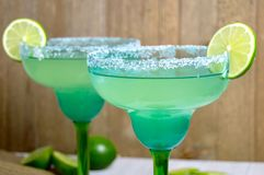 Margaritas with lime slices. Pair of salted margaritas with lime slices in festive blue and green glasses against a wooden background Royalty Free Stock Photo