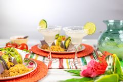 Margaritas with salt and limes and mexican food. Margaritas and Mexican food on colorful tabletop with blank space for copy
