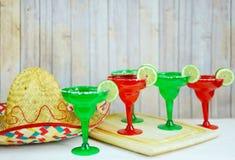 Margaritas in rode en groene glazen met gezouten randen en kalk versiert royalty-vrije stock afbeelding