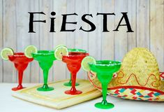 Margaritas in rode en groene glazen met gezouten randen en kalk versiert stock foto