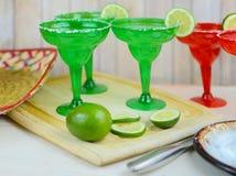 Margaritas in rode en groene glazen met gezouten randen en kalk versiert royalty-vrije stock foto's