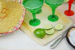 Margaritas in rode en groene glazen met gezouten randen en kalk versiert stock fotografie
