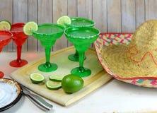 Margaritas in rode en groene glazen met gezouten randen en kalk versiert royalty-vrije stock fotografie