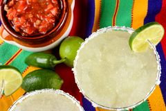 Margaritas and Salsa on a colorful table cloth, with limes, and. Cinco de Mayo Concept: Margaritas and Salsa on a colorful table cloth, with limes, and peppers