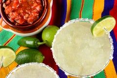 Margaritas y salsa en un mantel colorido, con las cales, y