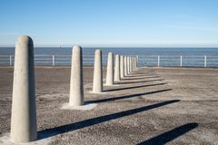 Concrete bollards casting shadows on the promenade by the sea in Margate stock image