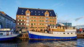 Margem de Nyhavn, canal, fachadas coloridas da reflexão velha da casa, e construções, navios, iate e barcos em Copenhaga, Dinamar foto de stock