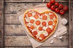 Margherita en forme de coeur de pizza avec des tomates Image libre de droits