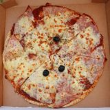 Margherita pizza cut into individual pieces. In its delivery box royalty free stock photography