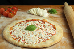 Margherita Pizza preparation. A  Margherita pizza with mozzarella, basil and tomato Royalty Free Stock Photography
