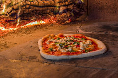 Margherita pizza in a wood oven. Margherita pizza in a traditional wood oven Italian Stock Images