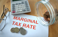 Marginal tax rate. With coins on paper and in pot and calculator behind Royalty Free Stock Image