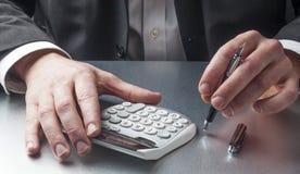 Marginaler och kostnader för manlig revisor couting på hans skrivbord royaltyfria bilder
