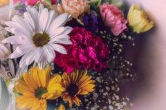 Marguerites colorées et d'autres fleurs dans un bouquet sur un fond de toile Image stock