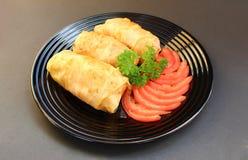 Marguerites cuites d'un plat avec des tomates et des herbes images stock