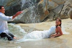 Marié éclaboussant la mariée des baisses d'eau de mer Photo libre de droits