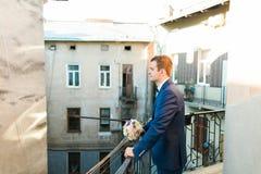 Marié élégant mignon dans le costume bleu et noeud papillon avec un bouquet des roses se tenant au balcon regardant vers Photographie stock