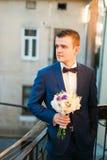 Marié élégant mignon dans le costume bleu et noeud papillon avec un bouquet des roses se tenant au balcon regardant vers Photos stock
