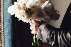 Marié élégant tenant le bouquet étonnant des roses et des feuilles d'or Image libre de droits