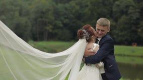 Mari? avec la jeune mari?e dans le voile nuptiale pr?s du lac en parc Couples de mariage banque de vidéos