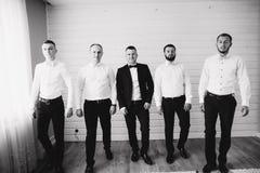 Marié beau avec son garçon d'honneur à la maison De cinq hommes Marié habillé dans le costume, gromsmen dans la chemise blanche T photo stock