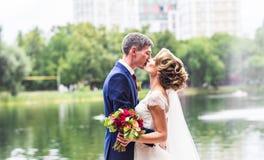Marié beau de brune embrassant la belle jeune mariée dans la robe de mariage Image libre de droits