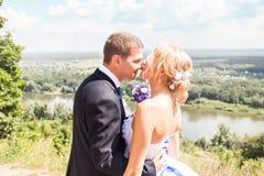 Marié beau de brune embrassant la belle jeune mariée dans la robe de mariage Photo stock
