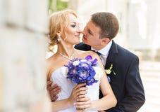 Marié beau de brune embrassant la belle jeune mariée dans la robe de mariage Photo libre de droits