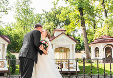 Marié beau de brune embrassant la belle jeune mariée dans la robe de mariage Photographie stock