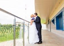 Marié beau de brune embrassant la belle jeune mariée dans la robe de mariage Photos stock