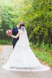 Marié beau de brune embrassant la belle jeune mariée dans la robe de mariage Image stock