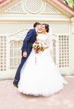 Marié beau de brune embrassant la belle jeune mariée dans la robe de mariage Photos libres de droits