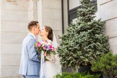 Marié beau de brune embrassant la belle jeune mariée dans la robe de mariage Images stock