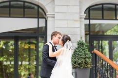 Marié beau de brune embrassant la belle jeune mariée dans la robe de mariage Images libres de droits