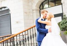 Marié beau embrassant la belle jeune mariée dehors Photo stock