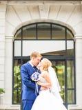 Marié beau embrassant la belle jeune mariée dehors Photos libres de droits