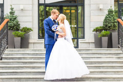 Marié beau embrassant la belle jeune mariée dehors Image stock