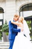 Marié beau embrassant la belle jeune mariée dehors Photographie stock