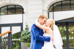 Marié beau embrassant la belle jeune mariée dehors Image libre de droits