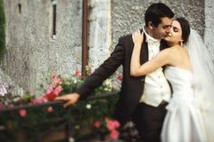 Marié beau et jeune mariée sexy de brune étreignant sur le vieil ove de pont Photo stock
