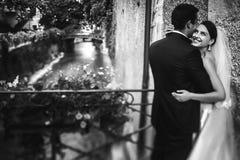 Marié beau et jeune mariée sexy de brune étreignant sur le vieil ove de pont Photo libre de droits