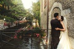 Marié beau et jeune mariée sexy de brune étreignant sur le vieil ove de pont Images stock