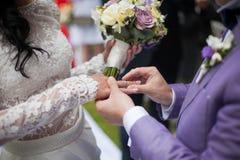 Marié beau mettant sur l'anneau sur la jeune mariée au plan rapproché de bas-côté de mariage Photographie stock