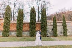 Marié beau posant avec son épouse près de la rangée d'arbre de cyprès et mur enrichi comme fond en parc romantique Photo stock