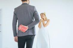 Marié cachant le boîte-cadeau rouge derrière le dos afin d'étonner la jeune mariée le jour du mariage, émotion positive de femme  images stock