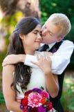 Marié caucasien embrassant affectueusement sa jeune mariée biracial sur la joue Di image stock