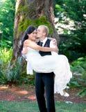 Marié caucasien portant sa jeune mariée biracial dehors, avec un KIS Photographie stock libre de droits