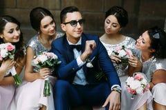 Marié dans les lunettes de soleil entourées par les demoiselles d'honneur avec du charme Photographie stock