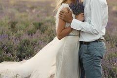 Marié dans une chemise blanche et une jeune mariée dans une robe de couleur blanche dans un domaine de lavande avec un bouquet de image stock